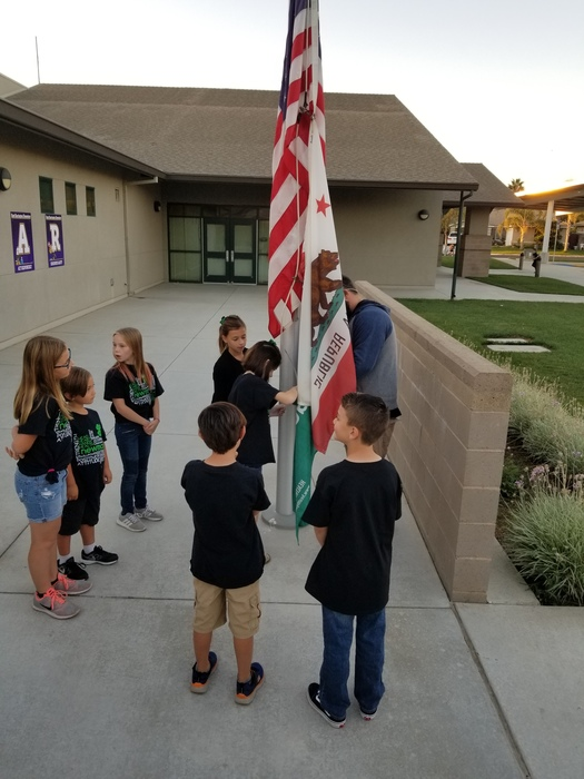 Addison Martins, 4-H student, helping to raise the flag at Barrington Elementary