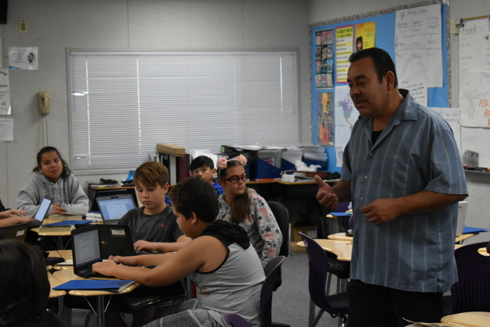 Mr. Garcia helping his students on Chromebooks