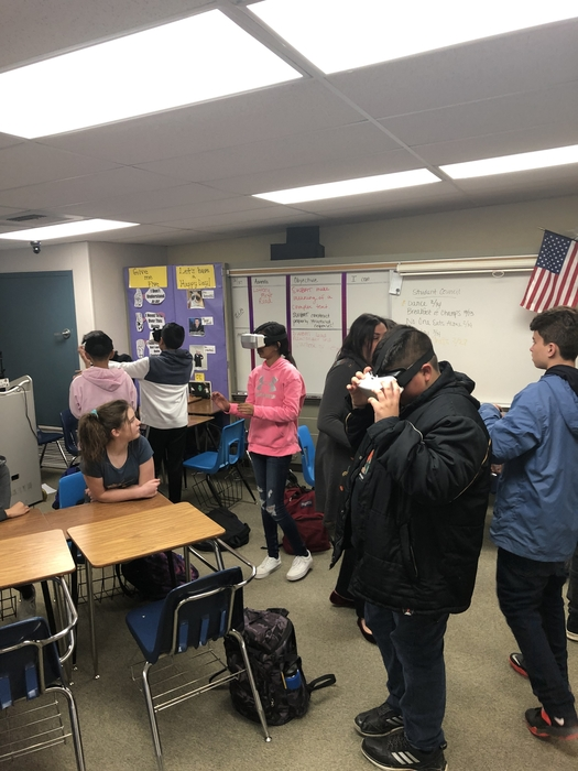 Students move around the room to explore the VR setting.
