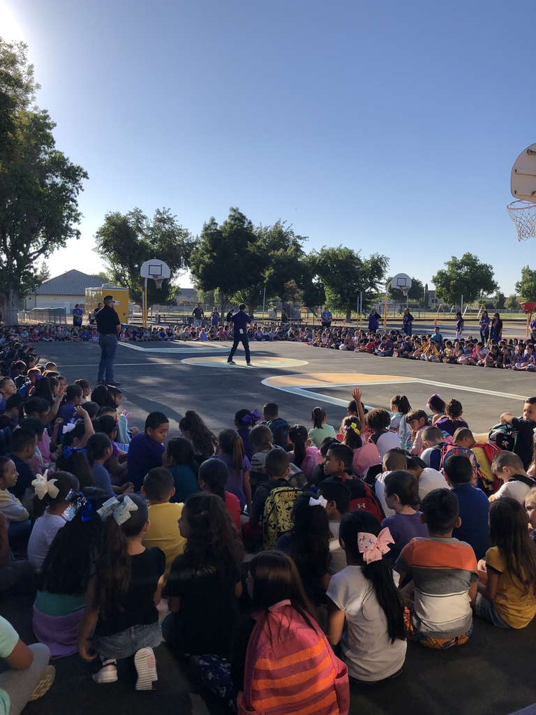 Students sitting on the blacktop at our assembly.