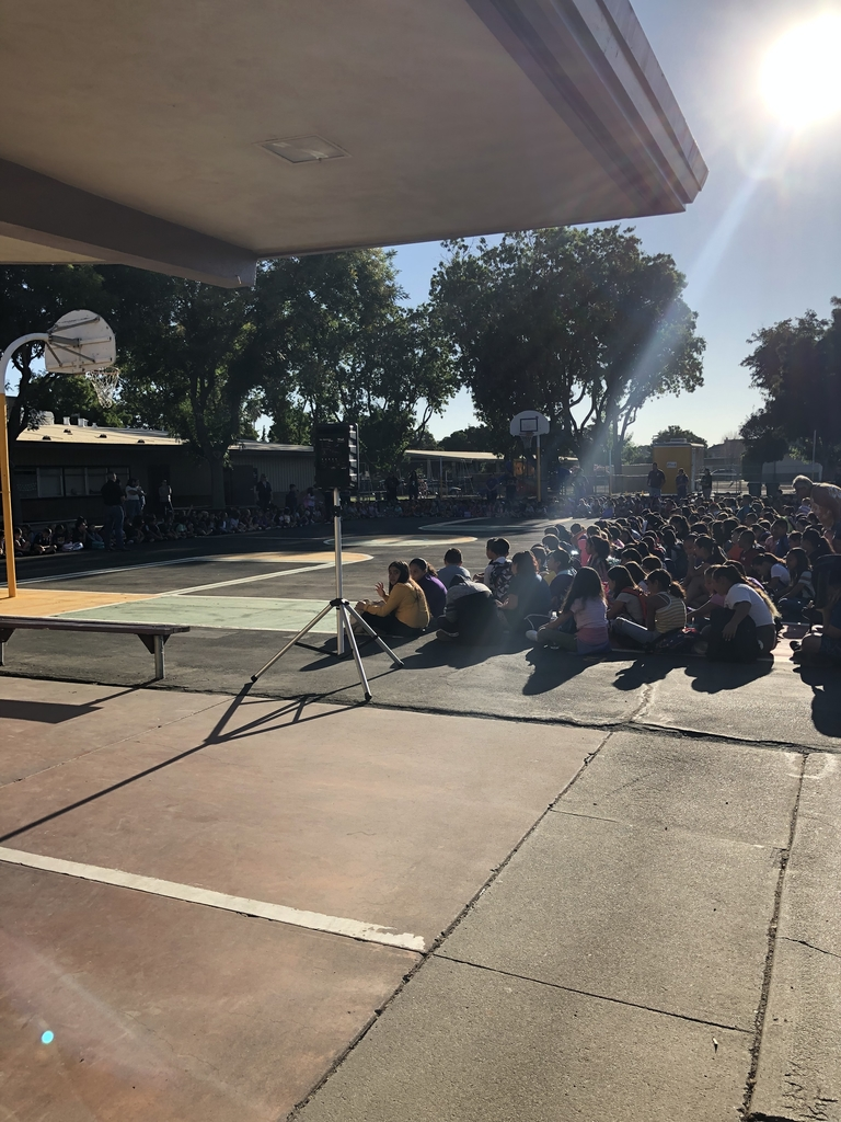 Students sitting on the blacktop for our assembly.