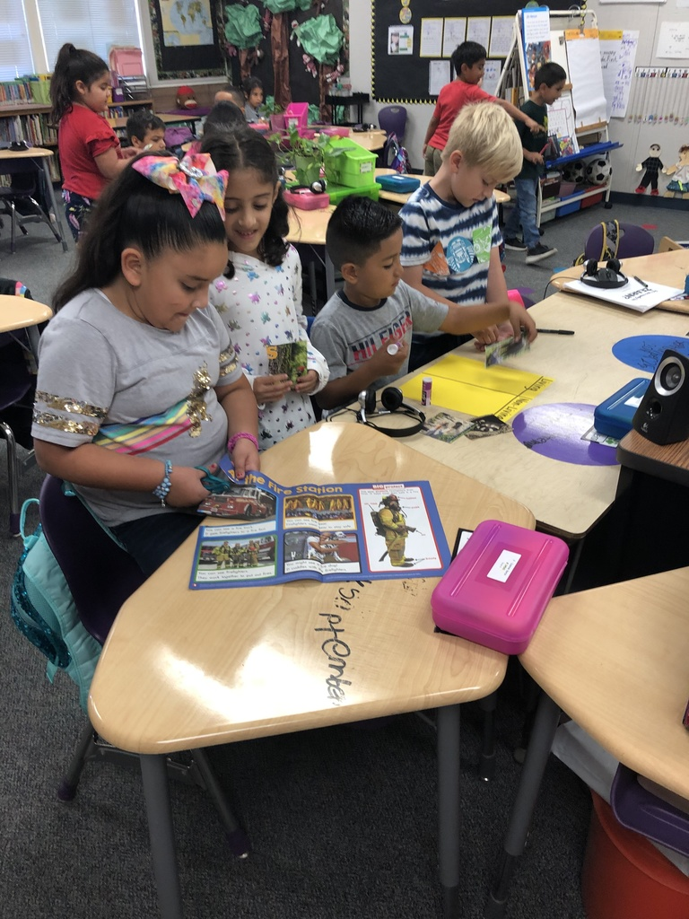 Mrs. Sunde's class collaborating on living and non-living things. Cutting pictures out of magazines and classifying them.