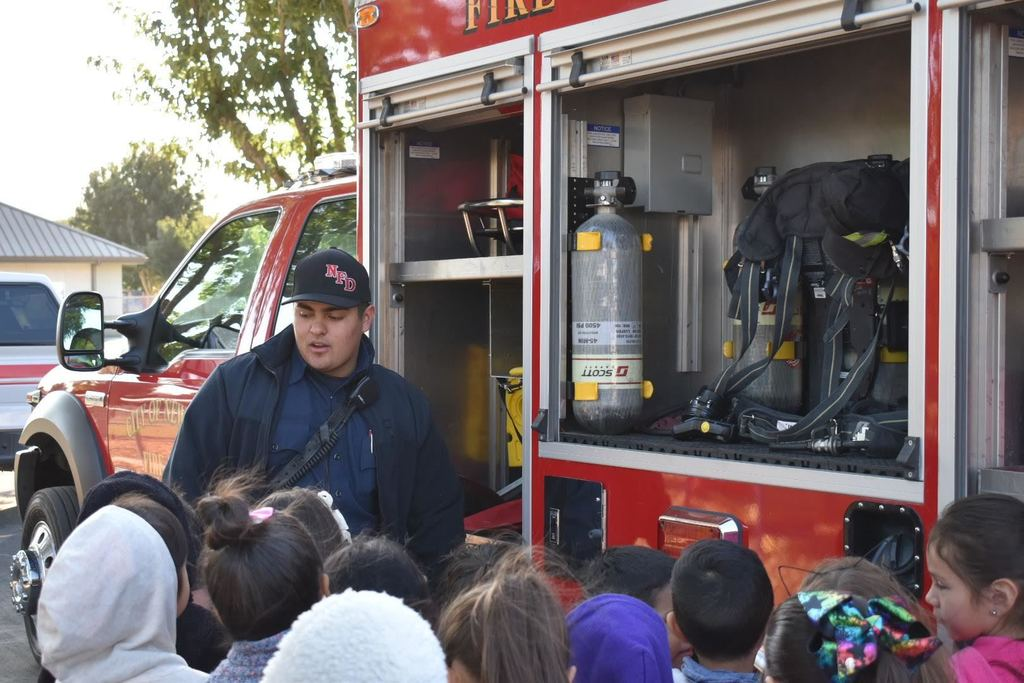Firefighter Miguel showing students the truck