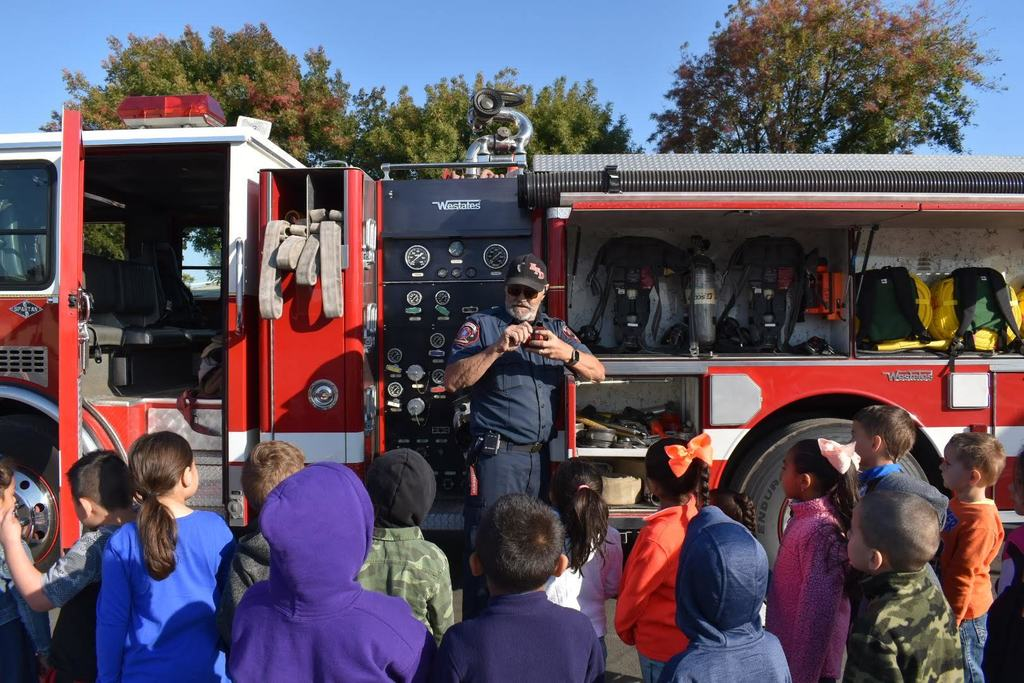 Firefighter Hurst showing students tools