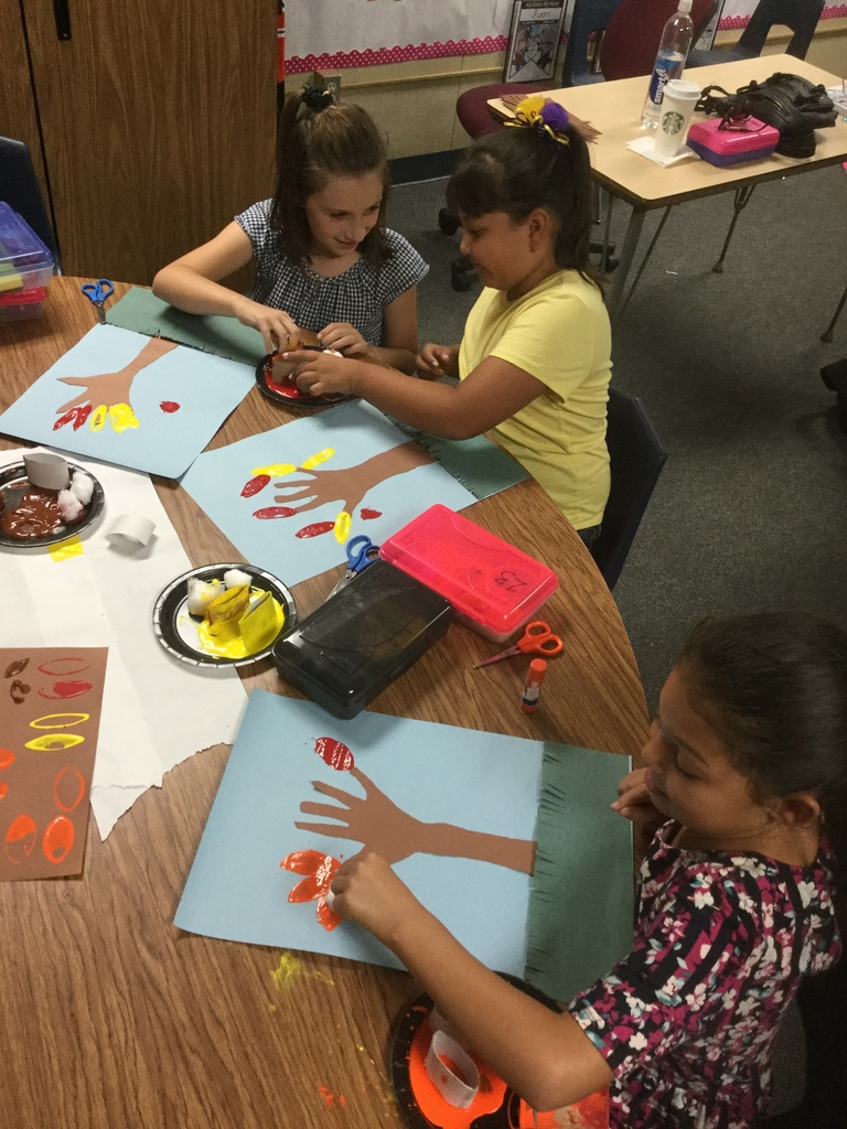 Students painting fall trees after learning about why leaves change color in the Fall.